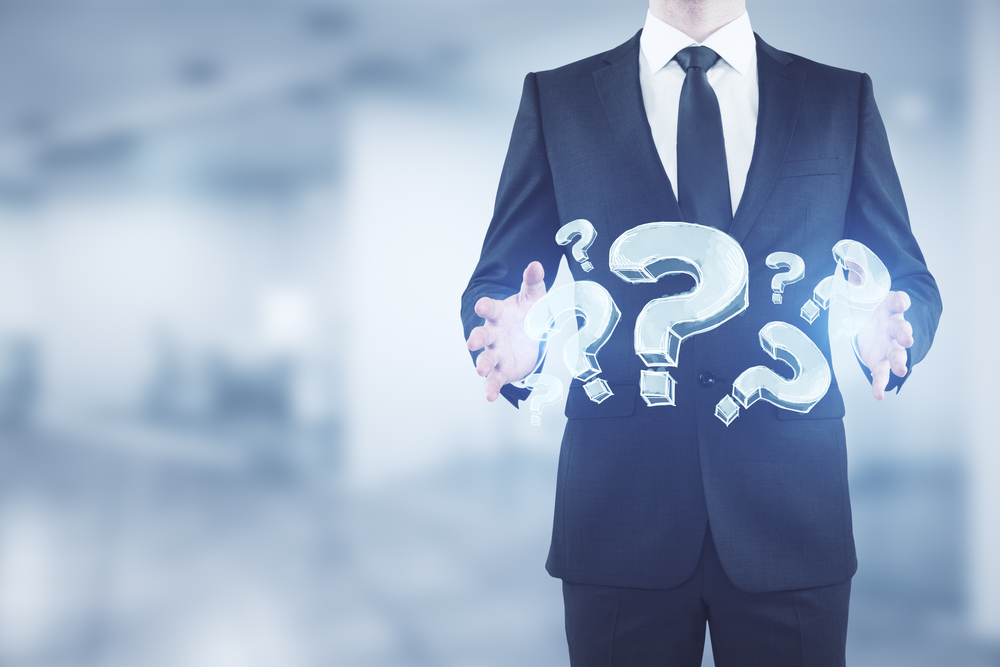 Image of a Businessman holding abstract glowing question marks